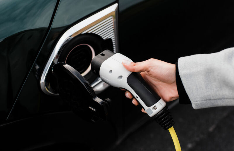 woman's hand plugging in a charger in an electric car socket